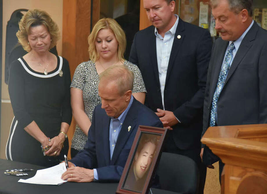 "Conor Vesper's mother, Alice, left, gets emotional as Gov. Bruce Rauner signs into law ""Conor's Law,"" which will require police to hold an underage DUI suspect until the individual is sober, or until they are picked up by a responsible adult. Conor Vesper died from a self-inflicted gunshot wound in 2015 after he was arrested and subsequently released on bond while still intoxicated. Photo: Tom Emery 