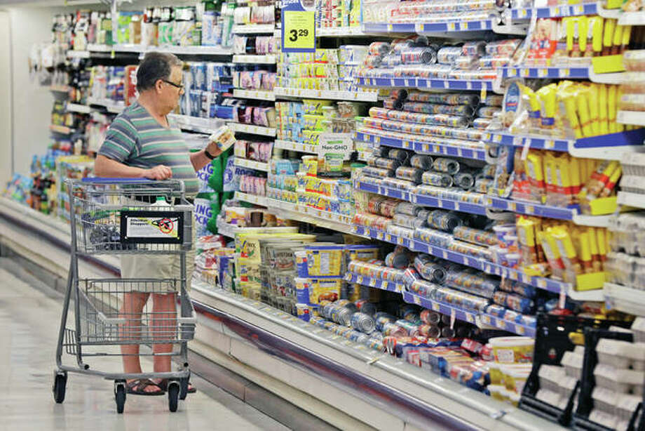 "A shopper looks at an item in the dairy section of a Kroger grocery store in Richardson, Texas. Some of the world's biggest consumer goods companies have agreed to simplify food date labels that create confusion among shoppers and leads them to discard billions of dollars' worth of food. The goal: to streamline the labels, including ""Sell by"" and ""Display until,"" down to two by 2020. Photo: LM Otero 