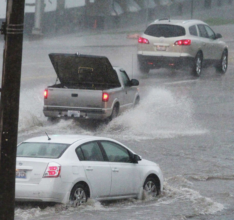 Scott Cousins/The Telegraph Vehicles work their way through the intersection of Piasa and Broadway during a severe storm early Tuesday afternoon. Driving winds and rain caused some shortlived street flooding in downtown Alton.