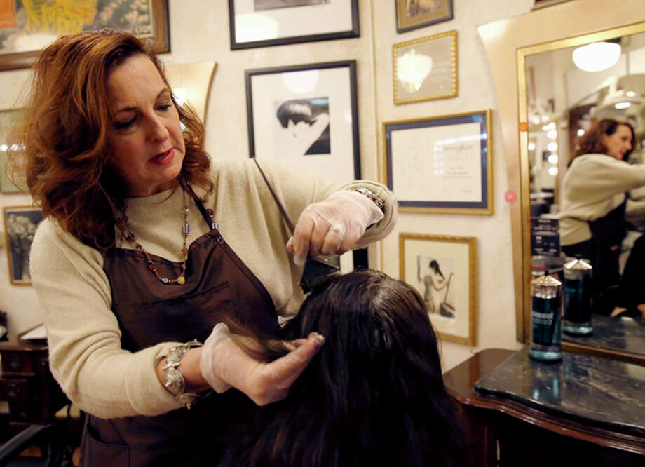 In this Thursday, Dec. 29, 2016, photo, Karen Gordon, left, works on the hair of a client at J. Gordon Designs in Chicago. The state law requiring one hour of abuse-prevention training for stylists, barbers, cosmetologists, estheticians, hair braiders and nail technicians as part of the licensing process that went into effect Sunday, Jan. 1. The National Conference of State Legislatures says the Illinois measure appears to be the first of its kind in the country.