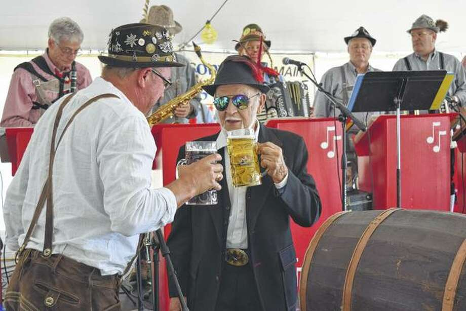Jacksonville Rotarian Paul Kluge (left) has a beer with his father, Heinz Kluge of Jacksonville, after the elder Kluge tapped the ceremonial keg Saturday at Rotary's annual Oktoberfest fundraiser at the Morgan County Fairgrounds. Heinz Kluge is a native of Brandenburg, Germany. Photo: Greg Olson | Journal-Courier