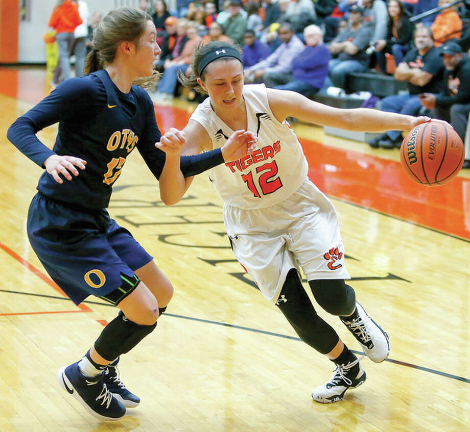 Edwardsville's Makenzie Silvey (12) drives against O'Fallon's Marta Durk (12) in SWC action Thursday night in Edwardsville. Silvery scored 16 points in the Tigers' 62-52 victory. Photo: Scott Kane | For The Telegraph