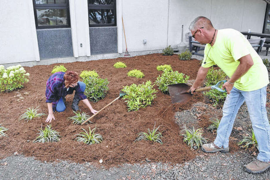 Jacksonville city employees Deanna WarBonnett (left) and Mike Woods spread mulch Tuesday around new landscaping in front of the Municipal Building.