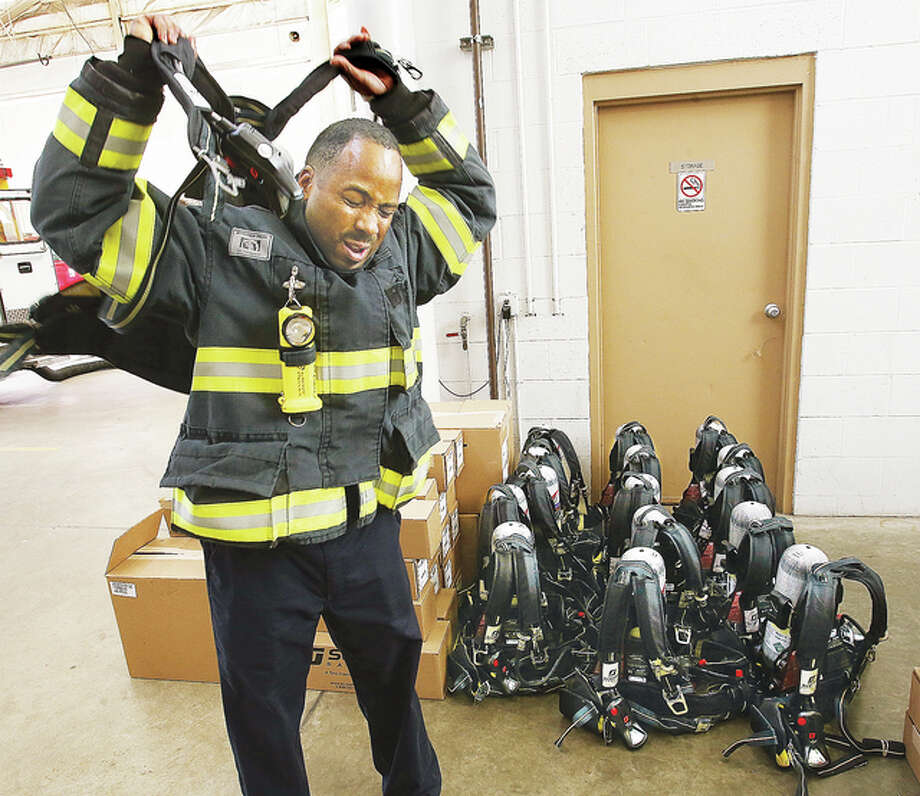 Alton Fire Department Capt. Derrick Richardson tries on one of Alton's new Scott-brand, self-contained breathing apparatus at the Don Twichell Memorial Fire Station 1. Alton has purchased 16 packs, 32 air cylinders, supporting equipment including a locator for downed firefighters, with money from a federal, $108,182 grant that covered 90 percent of the cost.