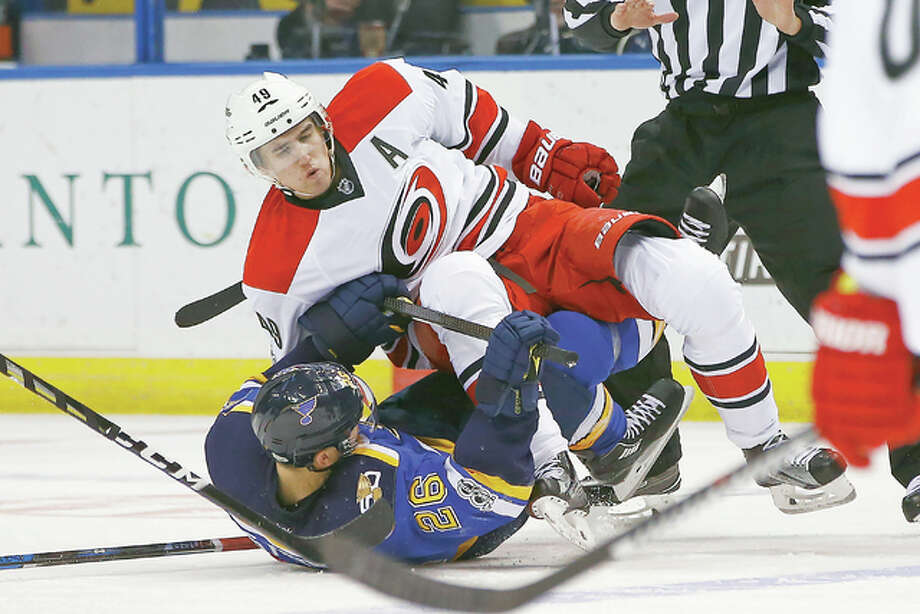 Carolina's Victor Rask, top, levels the Blues' Paul Stastny during the second period of Thursday's game in St. Louis. Photo: Billy Hurst | Associated Press