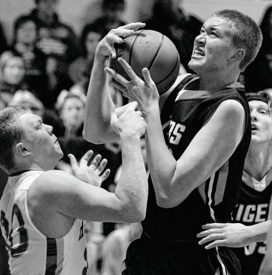 Greenfield's 6-foot-11 center Ben Bayless gains control of the ball during a game against Brown County on Saturday at the 95th annual Winchester Invitational Tournament. The Tigers defeated the Hornets 39-35 in a first-round game of a tourney that continues nightly through Saturday. Photo: Dennis Mathes / Journal-Courier