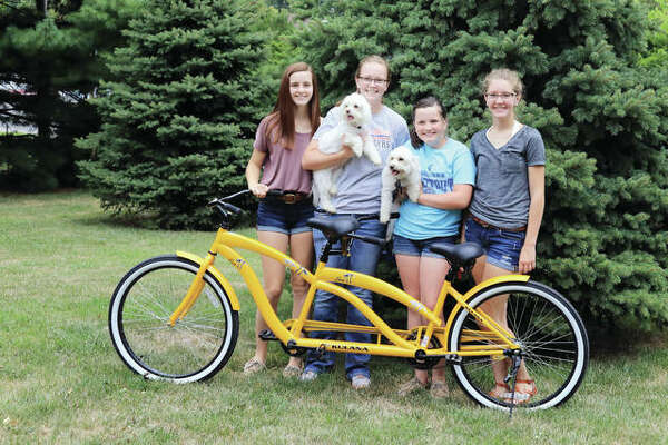 Sarah Robinson of Franklin won a tandem bicycle raffle held this summer by the Jacksonville Lions Club. Robinson's daughters - Ellie (from left), Kaylee, Sadie and Madison - were considering adding a basket so their dogs, Dixie and Wrigley, also can ride.