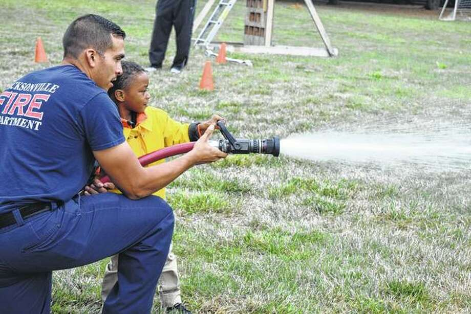 Jacksonville firefighter Ricky Padilla helps Ty Minner, 4, son of Meyonna Minner of Jacksonville, use a hose to complete the firefighter's challenge Saturday during the Jacksonville Fire Department's second annual open house. Photo: Samantha McDaniel-Ogletree | Journal-Courier
