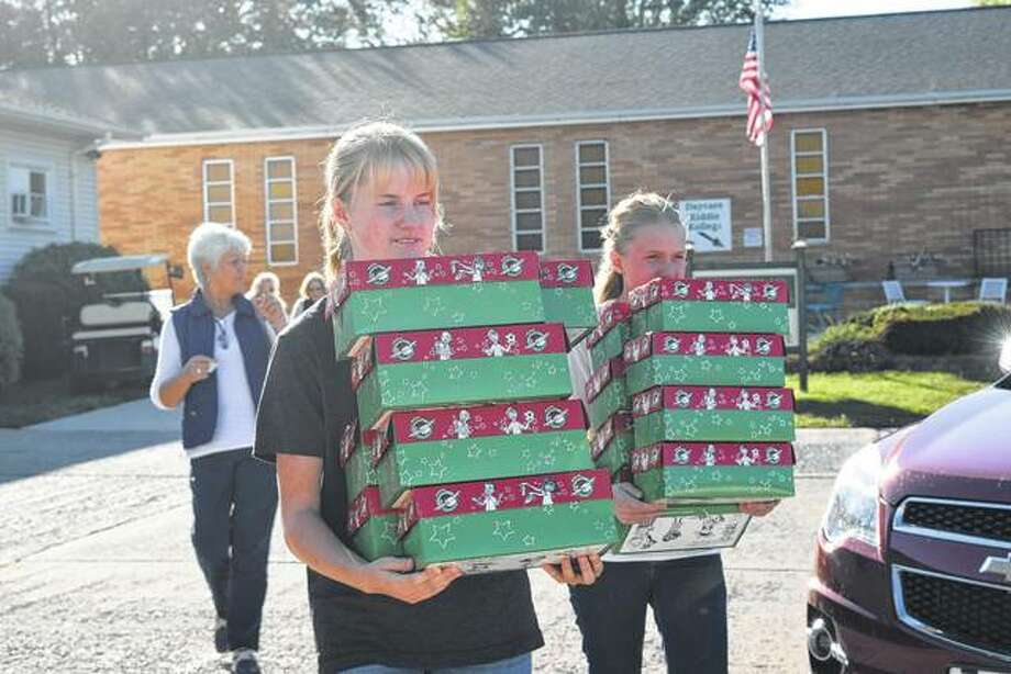 Faith and Emily Henthorn of Griggsville help carry shoeboxes Sunday afternoon during an Operation Christmas Child Shoebox Fair at Westfair Baptist Church. Operation Christmas Child is a project of the relief organization Samaritan's Purse in which shoeboxes are filled with small toys, hygiene items and school supplies and sent to children affected by famine, poverty, war and natural disasters. Photo: Audrey Clayton | Journal-Courier