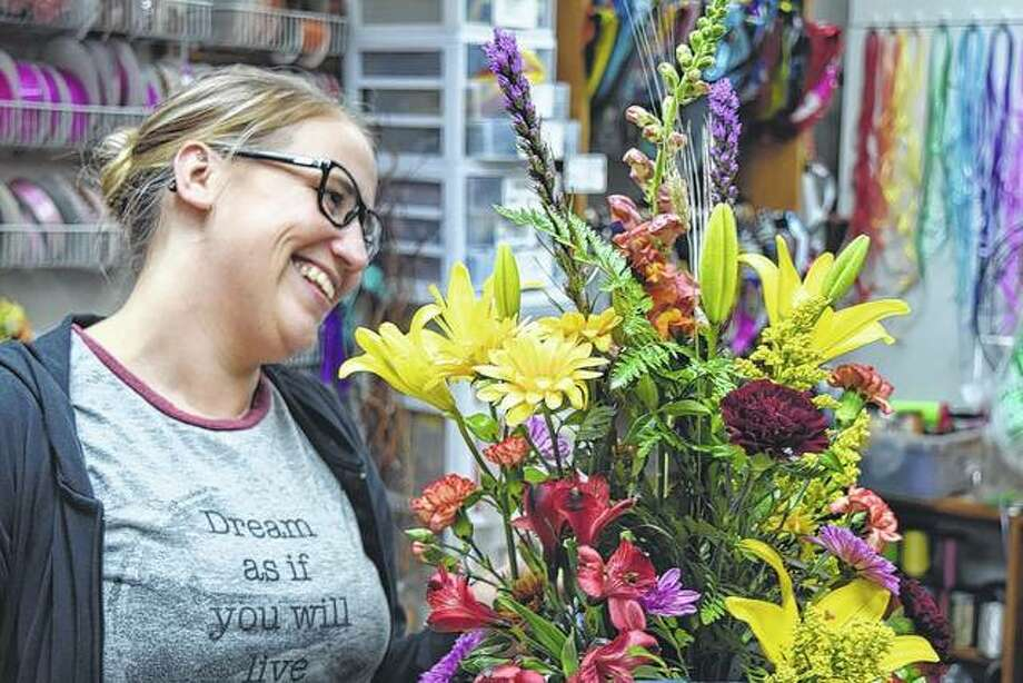 Ashley Scott of All Occasions Flowers and Gifts arranges a fall flower bouquet of yellow lilies, alstroemeria, Solidago, snapdragons and other assorted flowers.
