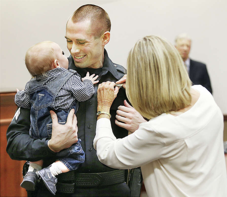 Alton Police Sgt. Jarrett Ford smiles at his son, Brady, as his mother, Patty Ford, pins his new badge on his chest at a police promotion ceremony Tuesday, where Ford was promoted to the rank of lieutenant. Ford will take over as chief of detectives of the Alton Police Department. A crowd of family, friends and well-wishers filled the courtroom at the Donald E. Sandidge Alton Law Enforcement Center to watch the promotions of five officers.