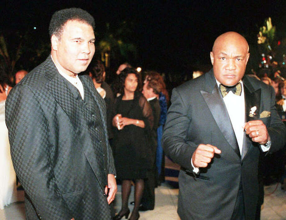 Boxing greats Muhammad Ali (left) and George Foreman arrive at a Vanity Fair Oscar party in West Hollywood, California, in 1997. Muhammad Ali Enterprises is suing the Fox Broadcasting Co. for more than $30 million for what it says was Fox's unauthorized use of the famed boxer's image in a video that ran just before its broadcast of the 2017 Super Bowl. The federal lawsuit was filed Tuesday in Chicago.