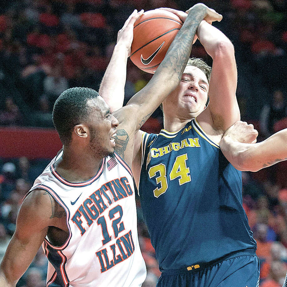 Illinois forward Leron Black (12) battles for a rebound with Michigan forward Mark Donnal Wednesday night in Champaign. Photo: Rick Danzl | AP