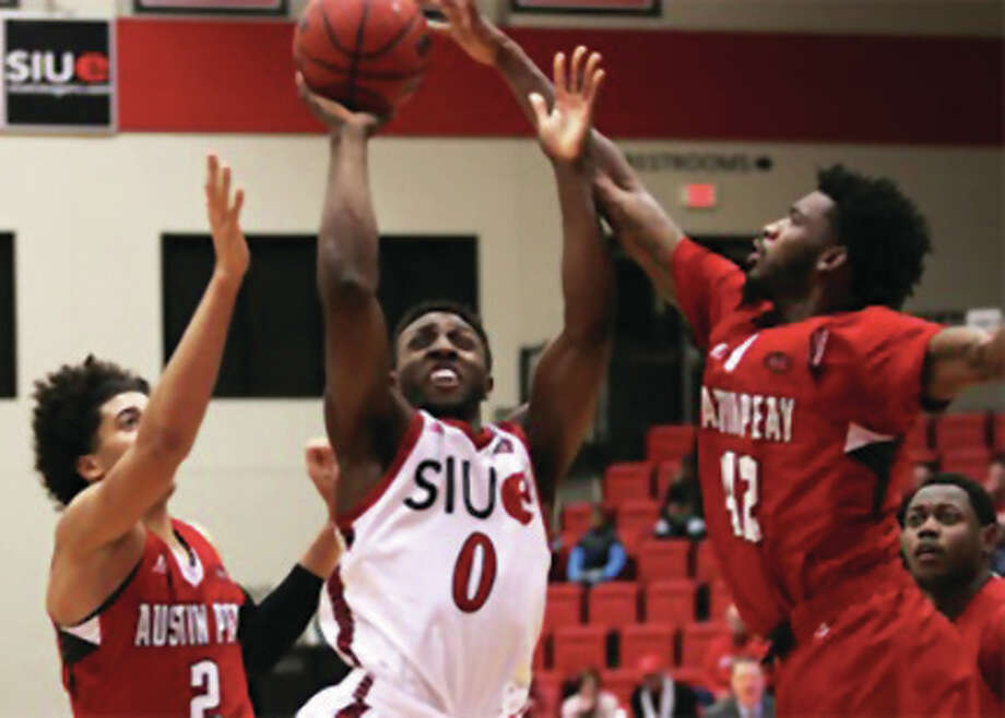 SIUE's Carlos Anderson, a sophomore from Alton, puts up a shot contested by Austin Peay's Jared Savage (left) and Kenny Jones (right) during Thursday night's OVC men's basketball game at Vadalabene Center in Edwardsville. Photo: SIUE Athletics