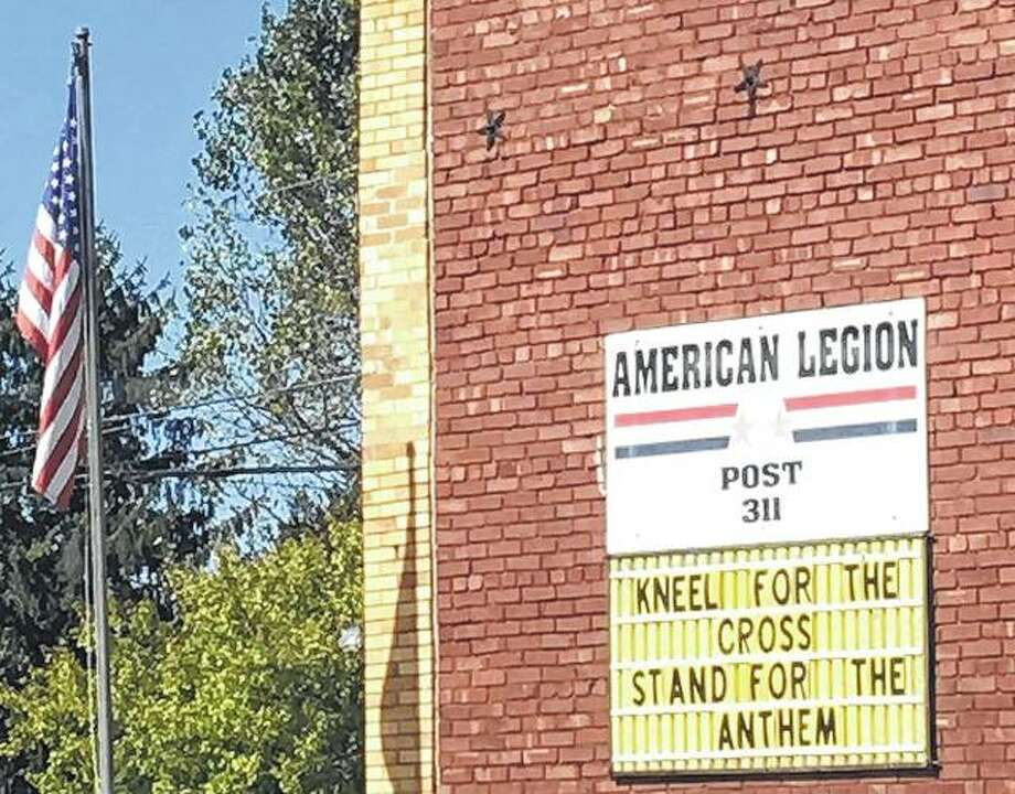 A sign on the side of the American Legion post in Murrayville gives a clear message about the controversy over football players taking a knee during the national anthem in protest. Photo: Joy Harris | Reader Photo