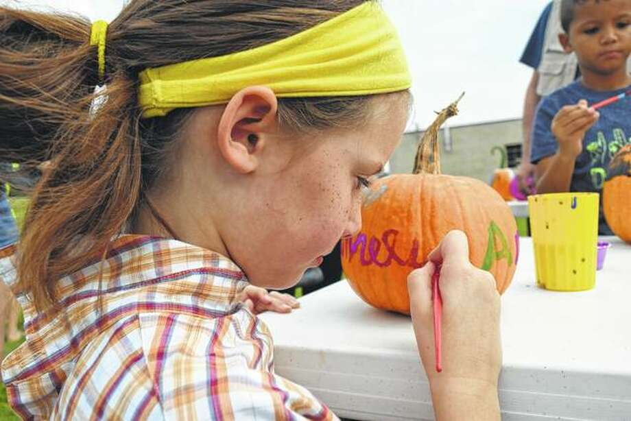 Amelia Olson, 8-year-old daughter of Audra and Michael Olson of Springfield, paints her name on a pumpkin Saturday at the Jacksonville Church of Christ's Fall Festival. Photo: Greg Olson | Journal-Courier