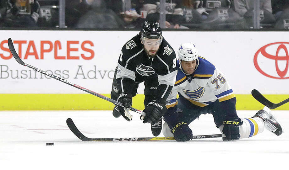 Los Angeles Kings defenseman Drew Doughty, left, vies for the puck with Blues right winger Ryan Reaves dThursday night in Los Angeles.