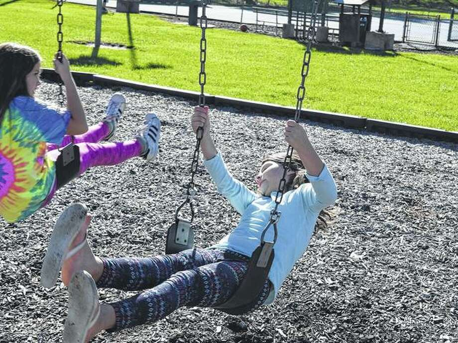 Regan Vannoy (left), 10, and Chatyn Besterfeldt, 8, play on the swing set Monday during the after-school program at Bob Freesen YMCA. Photo: Samantha McDaniel-Ogletree | Journal-Courier