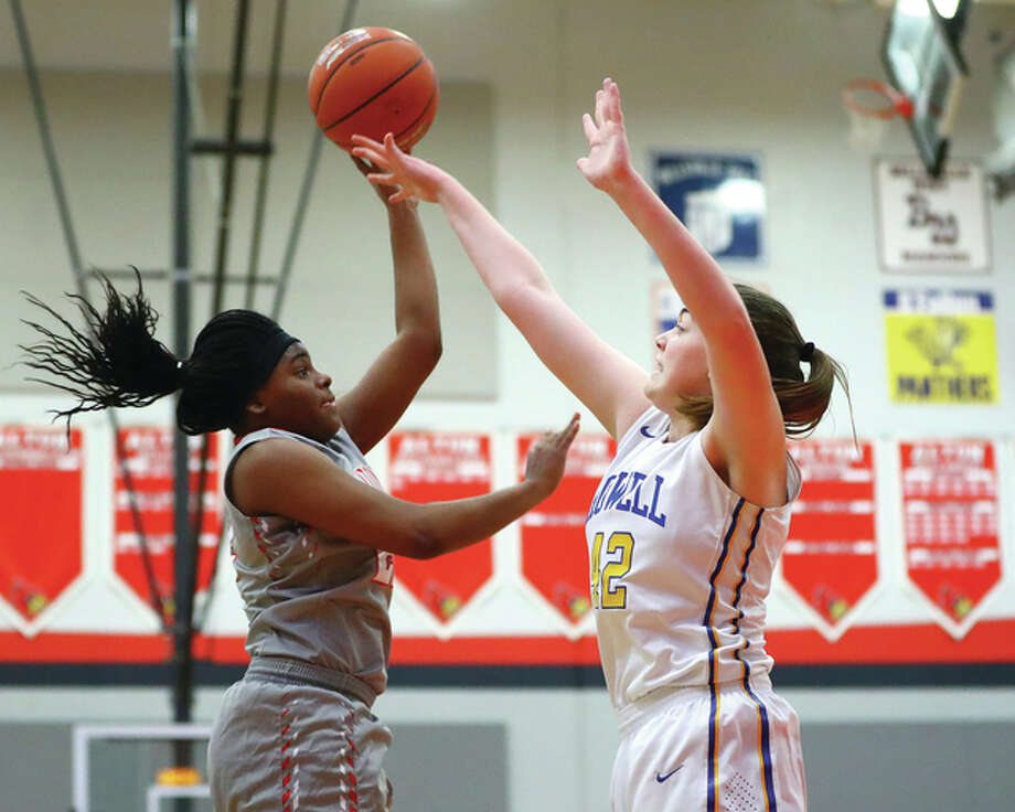 Alton's Cri'shonna Hickman (left) shoots over Francis Howell's Micah Huwe during the five-game Liberty Bank Great Rivers Shootout on Monday at Alton High School in Godfrey. Photo: Billy Hurst / For The Telegraph