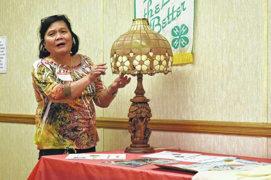 Glenda Mason showcases a lamp made in the Philippines with a seashell shade during the Morgan County Home and Community Education group International Day. Photo: Samantha McDaniel-Ogletree | Journal-Courier