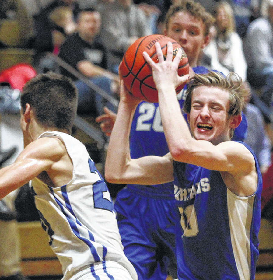 North Greene's Brett Whicker (right) grimaces as he avoids a Petersburg PORTA player on a fast break during the third-place game Monday at the Winchester Tournament. Photo: Dennis Mathes / Journal-Courier