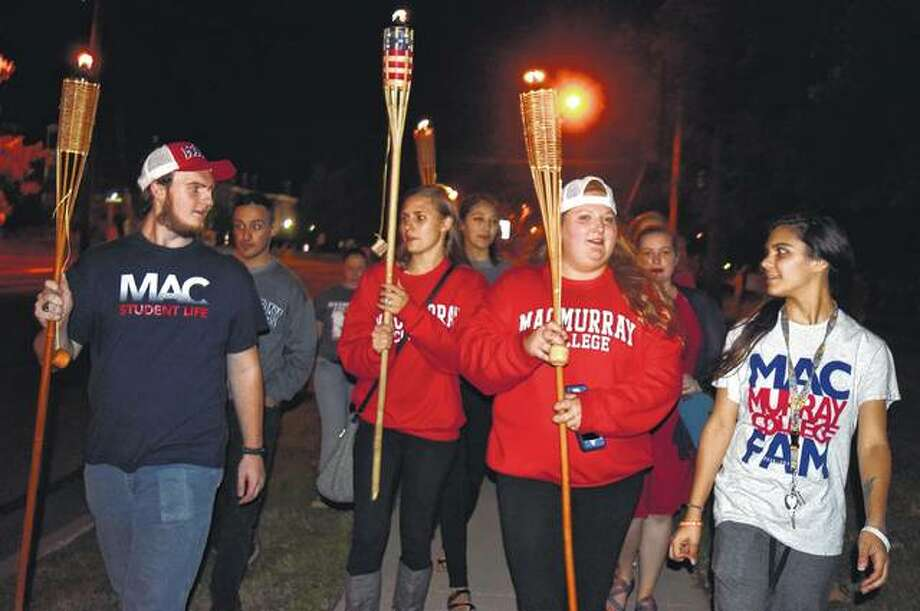 MacMurray College students Lucaas Secrist (left), a senior, Anastacia Maio, a junior, Kalyn Murre, a senior, and Alicia Day, a junior, lead the way as they marched through campus Friday night during the MacMurray College Torchlight Parade. The Torchlight Parade is a MacMurray homecoming tradition where students march through campus leading into the pep rally. Homecoming events at MacMurray continue today and Sunday. Photo: Samantha McDaniel-Ogletree | Journal-Courier
