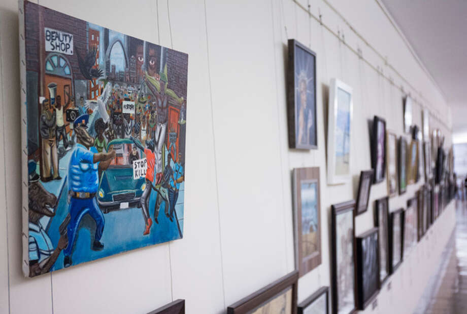In this Jan. 5, 2017 file photo, a painting by David Pulphus hangs in a hallway displaying paintings by high school students selected by their member of congress on Capitol Hill in Washington. A student's painting that divided members of Congress for its depiction of Ferguson, Mo., has been removed from its Capitol Hill display, this time more permanently.
