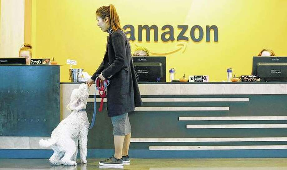 An Amazon employee gives her dog a biscuit as the pair head into a company building, where dogs are welcome, in Seattle. Amazon says it received 238 proposals from cities and regions hoping to be the home of the company's second headquarters. The online retailer kicked off its hunt for a second headquarters in September, promising to bring 50,000 new jobs. It will announce a decision in 2018.