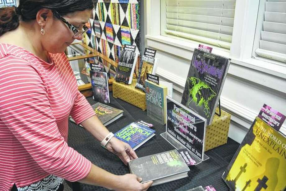 Jacksonville Public Library clerk Bridget Dean arranges a display of books related to the paranormal Tuesday at the library. Paranormal investigators Loren Hamilton and Sylvia Shults will give a presentation on ghost hunting at 7 p.m. Tuesday at the library. Photo: Greg Olson | Journal-Courier