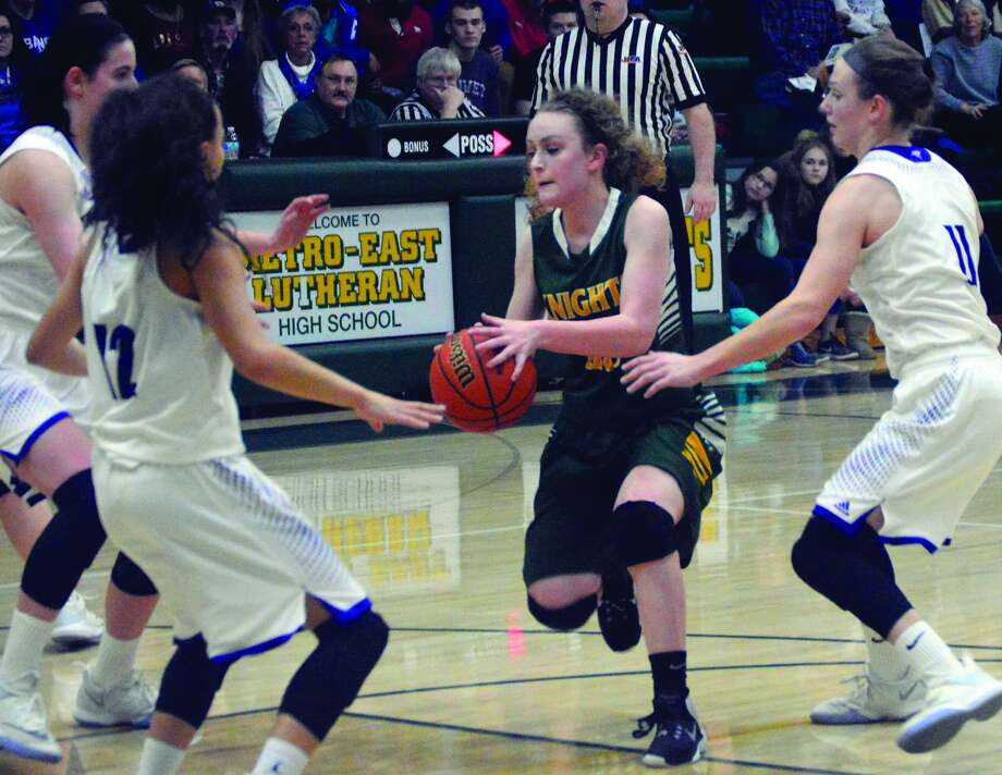 Metro-East Lutheran senior Maddie Stewart, center, dribbles into traffic in the first quarter of Friday's regional championship game against Lebanon.