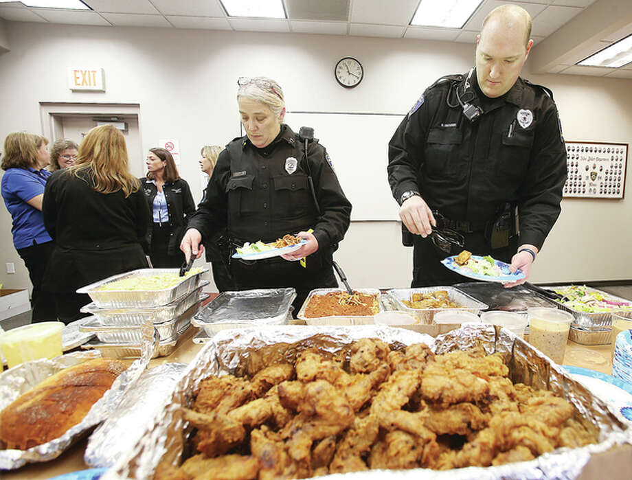 Nurses and other workers from the Case Management Department at Alton Memorial Hospital put on a spread of food for the Alton Police Department Friday from Alton's Tony's Restaurant. Officers Jennifer Doty, left, and Brian Brenner dish up some lunch inside the law enforcement center.