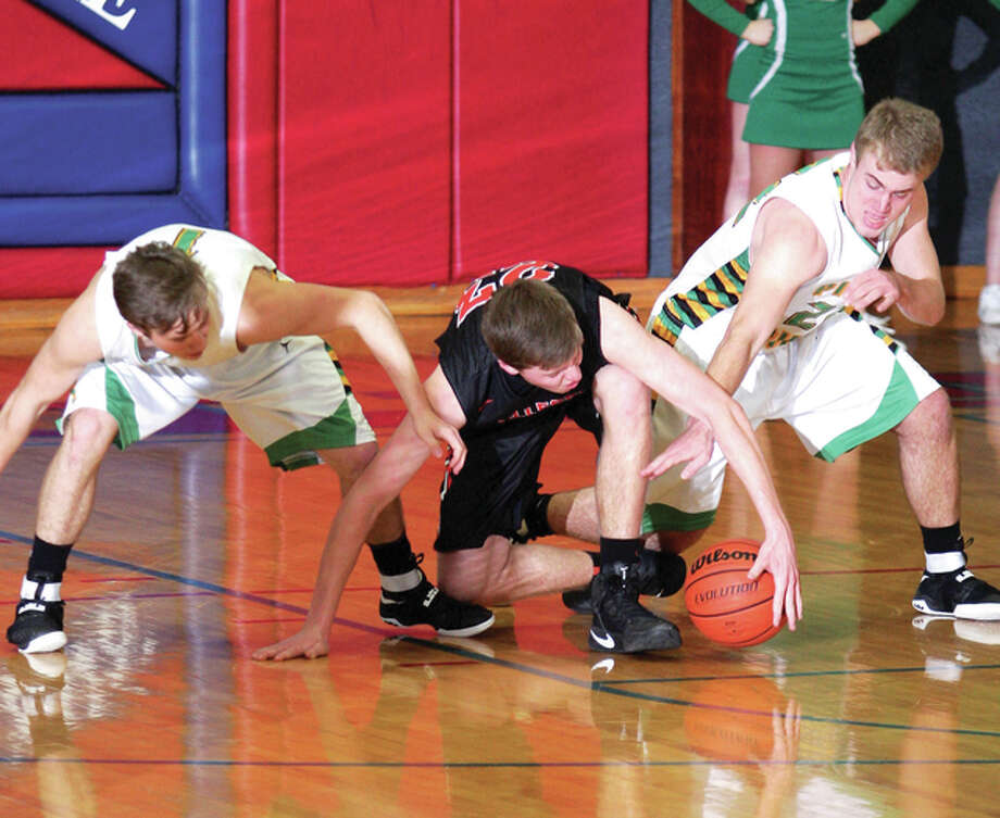 Gillespie's Nathan Davis tries to grab a loose ball as Southwestern's Justin Bailey, right, and Ben Lowis, Left, team up to steal it Friday night during the Macoupin County Tournament in Carlinville. Photo: James B. Ritter | For The Telegraph