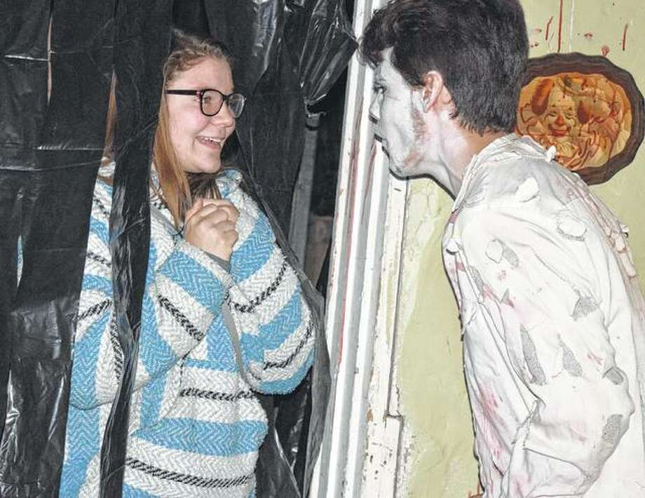 Paige Ehlenbeck of Winchester gets scared by Drake Gregory during the Winchester Civic Group haunted house Friday at the Winchester Old School Museum. The haunted house will continue from 5:30-10 p.m. A kid-friendly, lights-on family time and wiener roast will take place from 5:30-6:30 p.m. and is $10 per family. The haunted house will take place from 7-10 p.m. and is $5 per person. Photo: Samantha McDaniel-Ogletree | Journal-Courier