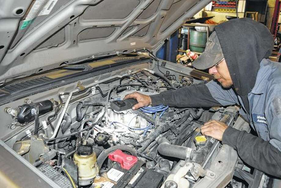 Auto technician Travis Million prepares to do engine work at Meadows Automotive. Million will take over the business, which is being renamed M&M Automotive, on Wednesday. Photo: Greg Olson | Journal-Courier