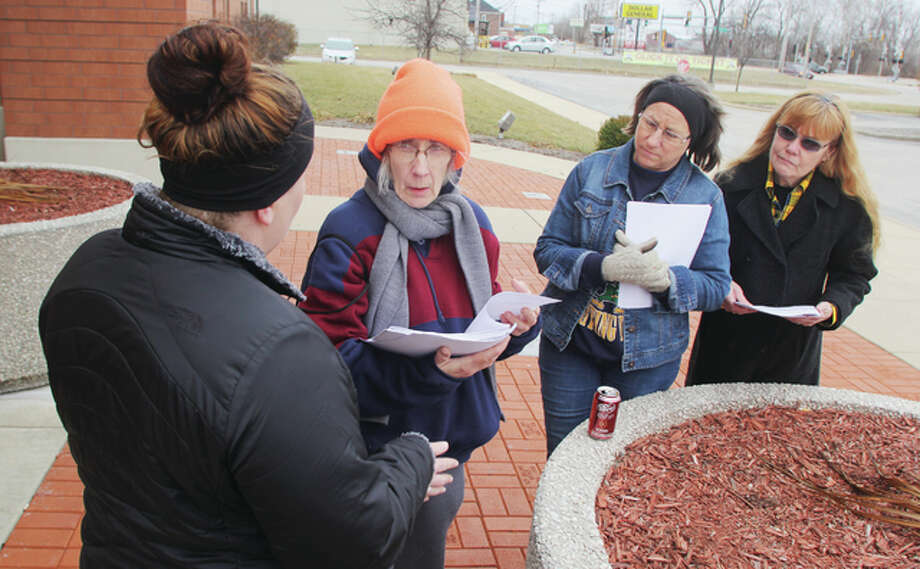 Brittany Pinnon, left, talks to volunteers Diane Martin, JoEllyn Paterson and Martha Rankin after handing out forms for Mondays homeless count. The group met in front of the Donald E. Sandidge Alton Law Enforcement Center before fanning out.
