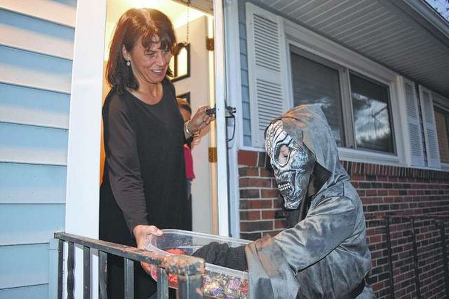 "Molly Stewart of South Jacksonville hands out candy Monday to Liam Campbell, 5, of South Jacksonville during trick-or-treating hours. Liam said he was dressed as ""the angel of death."" Trick-or-treating continues today."