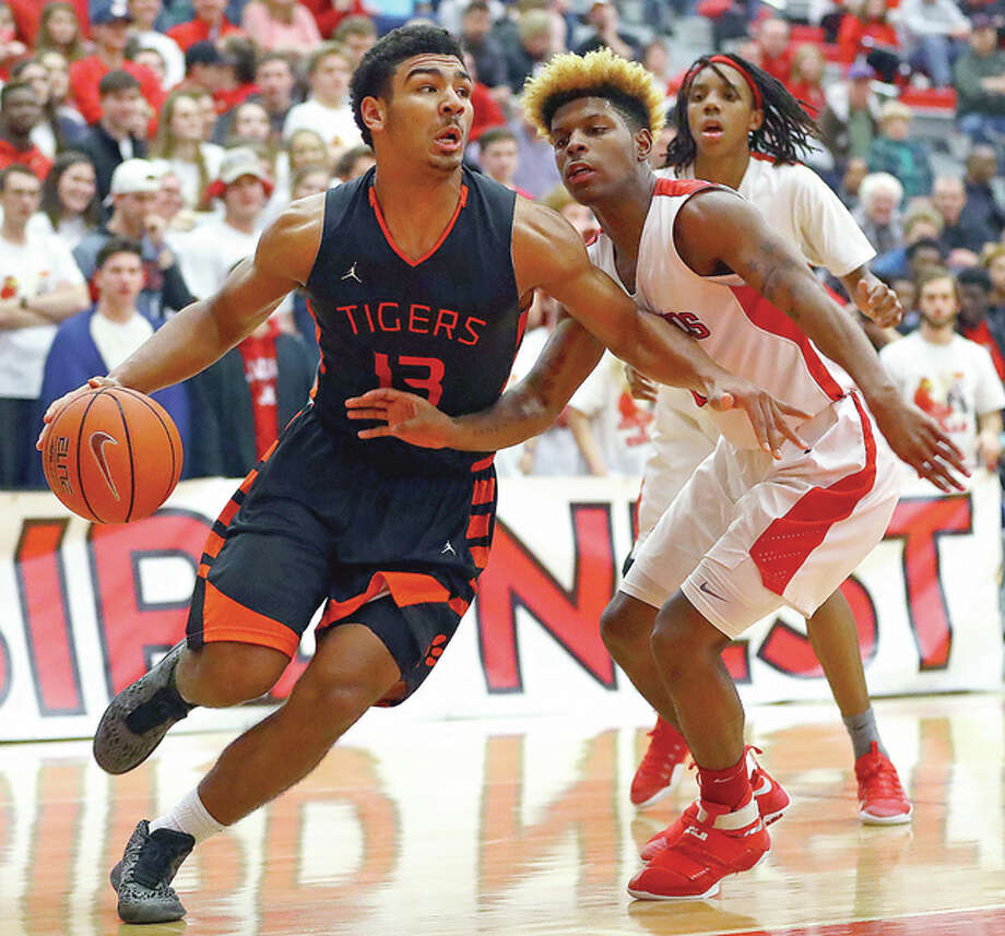 Edwardsville's Mark Smith, left, drives past Alton's Damion Reid during Tuesday night's game at Alton High School. Edwardsville won the game 59-48. Photo: Billy Hurst | For The Telegraph