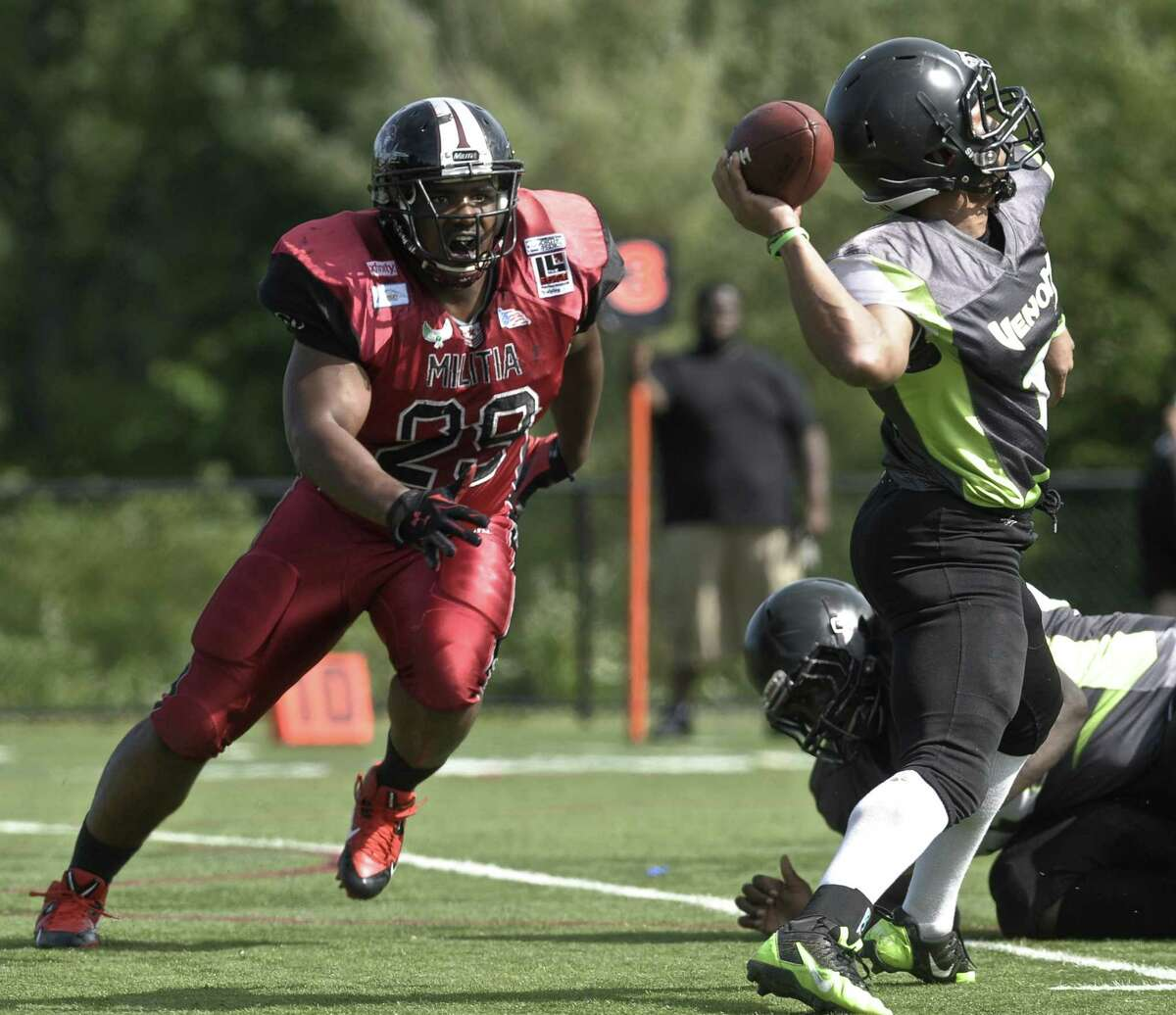 Ct Militia's Jasper Ramsey (29) closes in on New Haven's quarter back Andrew Smith (1) during a New England Football League pre-season game between the New Haven Venom and the Western Connecticut Militia at Rogers Park, in Danbury, Conn, on Saturday, June 13, 2015.
