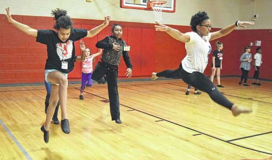 Fourth graders Autumn Gause (left) and Danijah White practice leaping with Illinois College pom team member Asia Watson Wednesday during a clinic between the Illinois College pom team and the Lincoln Elementary School pom team. Photo: Samantha McDaniel-Ogletree | Journal-Courier