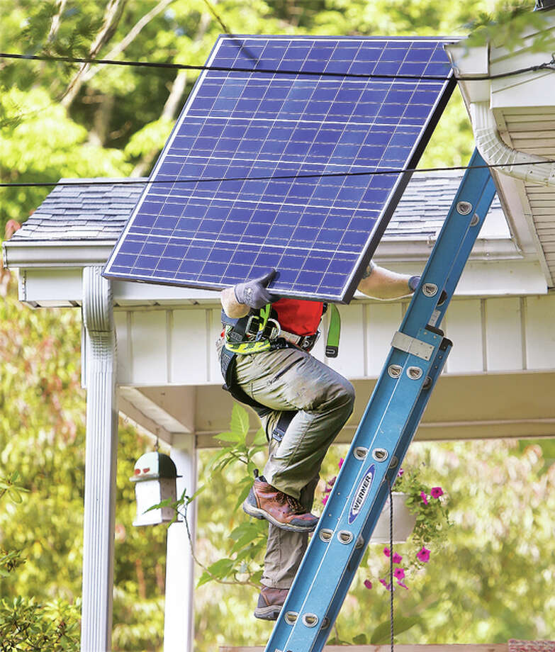 A worker carries a solar panel to the roof of a house in the 500 block of Mulberry Street in Godfrey over the summer.
