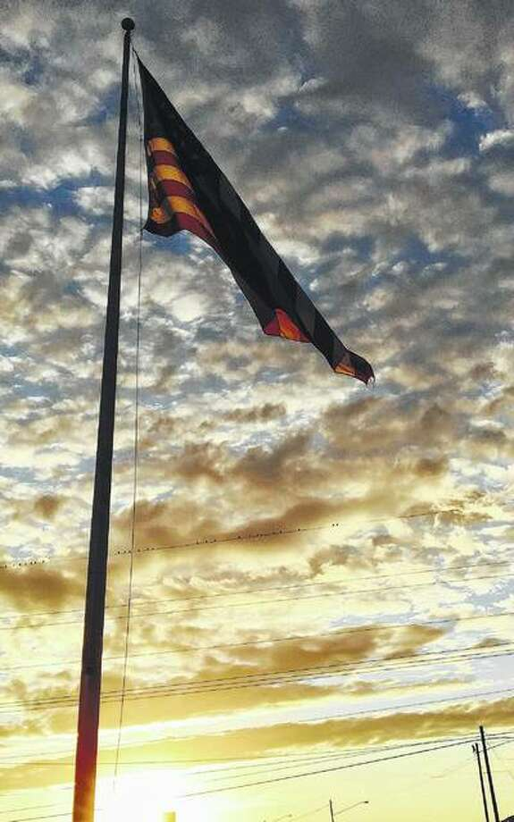 A flag waves with a cloud-filled sky as a background.