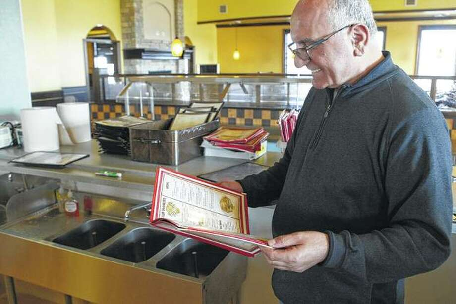 Agim Selimi looks over a menu at his new business, Mangia Restaurant and Bar, which is scheduled to open Thursday at 2210 W. Morton Ave.