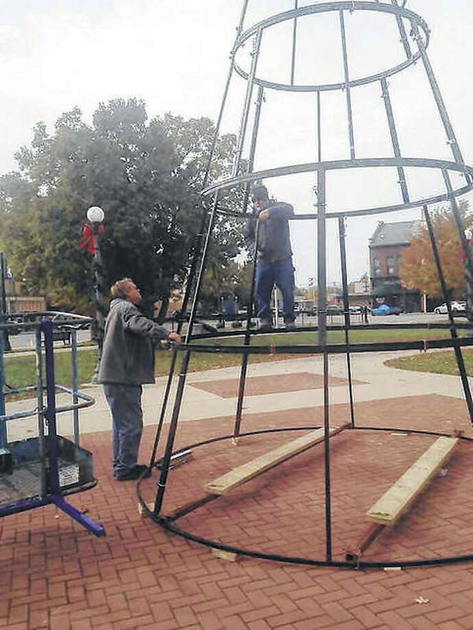 City employees Terry Chumley (left) and Terry Surratt work Tuesday on setting up the base for what will become the city's Christmas tree in downtown's Central Park. Crews will be working again today on getting the tree put together for the holiday season. Photo: Angela Bauer | Journal-Courier