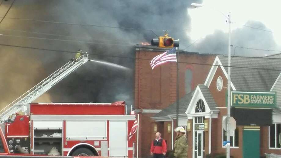 Firefighters attack the blaze with a ladder truck Tuesday morning in downtown White Hall.