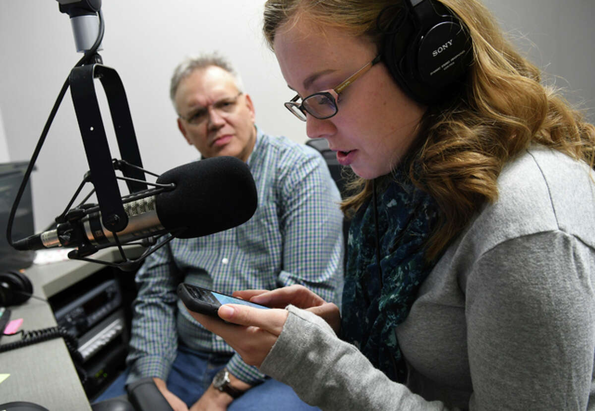 In this January 9, 2017 photo Lacy Scarmana, WVIK producer and co-host of the 'Suspect Convictions' podcast, works with her co-host, Scott Reeder, on recording an advertisement for the podcast at WVIK in Rock Island, Ill. 'Suspect Convictions' revisits the 1990 murder of Jennifer Lewis and the case against Stanley Liggins. In its first week, the podcast ranked in the top five of all U.S. podcasts on iTunes.