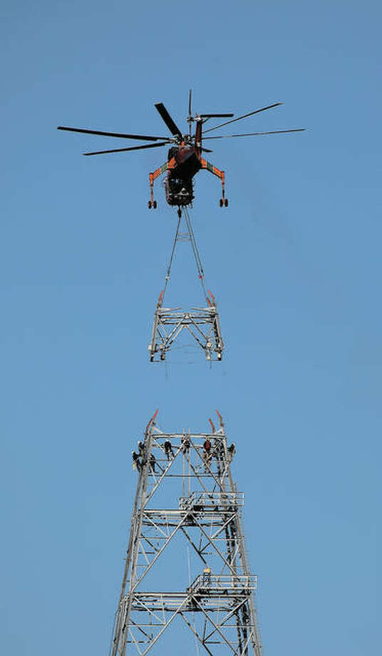 Ameren crews work Thursday to attach the tops of the towers along the Meredosia-Ipava route of the Illinois Rivers Transmission Project. Photo: Samantha McDaniel-Ogletree | Journal-Courier