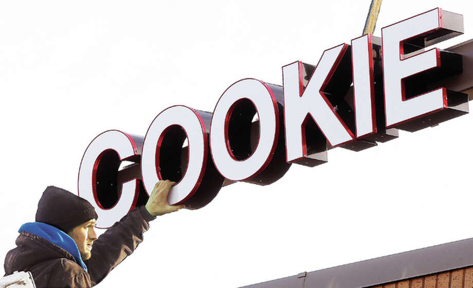 "John Landes, an employee of Arrow Outdoor Signs and Advertising, steadies part of a section of sign that says ""Cookie Factory"" Tuesday on the west side of Alton Square Mall, as he and a fellow crew member were working to put the lighted sign on the outside of the mall. The entire sign, located on the wall near the southernmost main entrance on the upper level of the mall, reads Cookie Factory & Cafe. It's the first permanent exterior sign allowed on the mall for a non-anchor store."