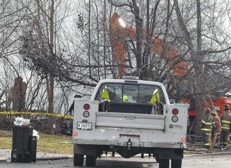 Firefighters gather at the site of a house fire in Franklin that claimed the lives of a mother and two children overnight Tuesday.