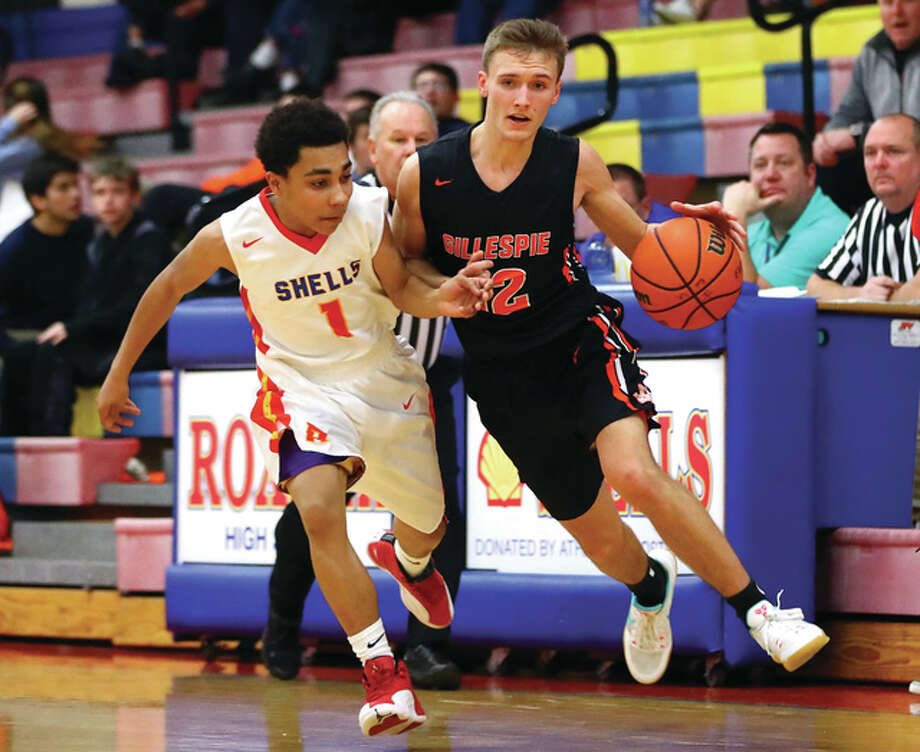 Gillespie's Nick Price (right) drives past Roxana's Mickey Ross during a South Central Conference boys basketball game Tuesday night at Larry Milazzo Gymnasium in Roxana. Photo: Billy Hurst / For The Telegraph