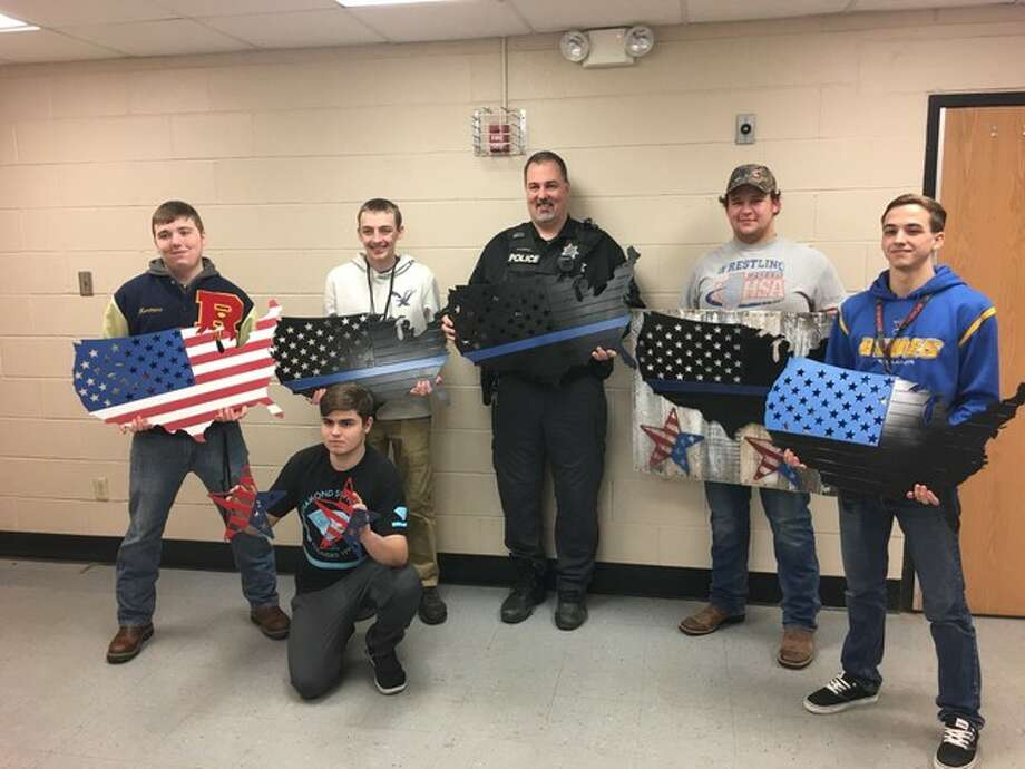 The officer pictured is South Roxana Officer Patrick Carrier and the shop students who created the signs. The plates the students are holding are, from left: Full Color US Support Flag, $100; the next three are The Spot Color US Flags - Police Support, $75; Back the Blue, $75; and in front the Freedom Star Painted, $25